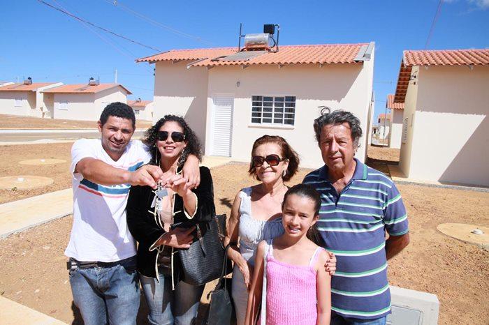 Família beneficiada com moradia no Residencial do Cerrado, em Anápolis. Na imagem um casal mais jovem,um casal da terceira idade e uma garotinha de aproximadamente  oio anos. Ao fundo as casas do residencial na cor bege.